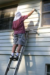 DIY home-owner painting the siding of his house.