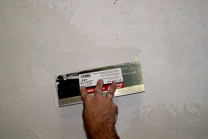 Applying drywall mud to a large wall repair.