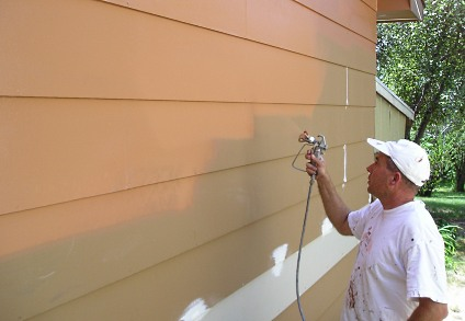 Spraying exterior paint on a home.