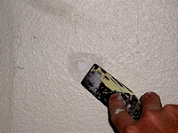 Filling small hole with spackling paste.