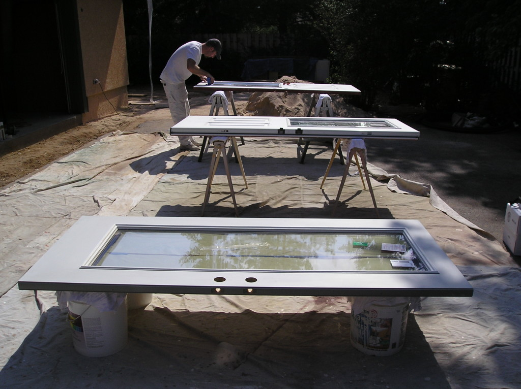 Spraying steel doors on saw horses.