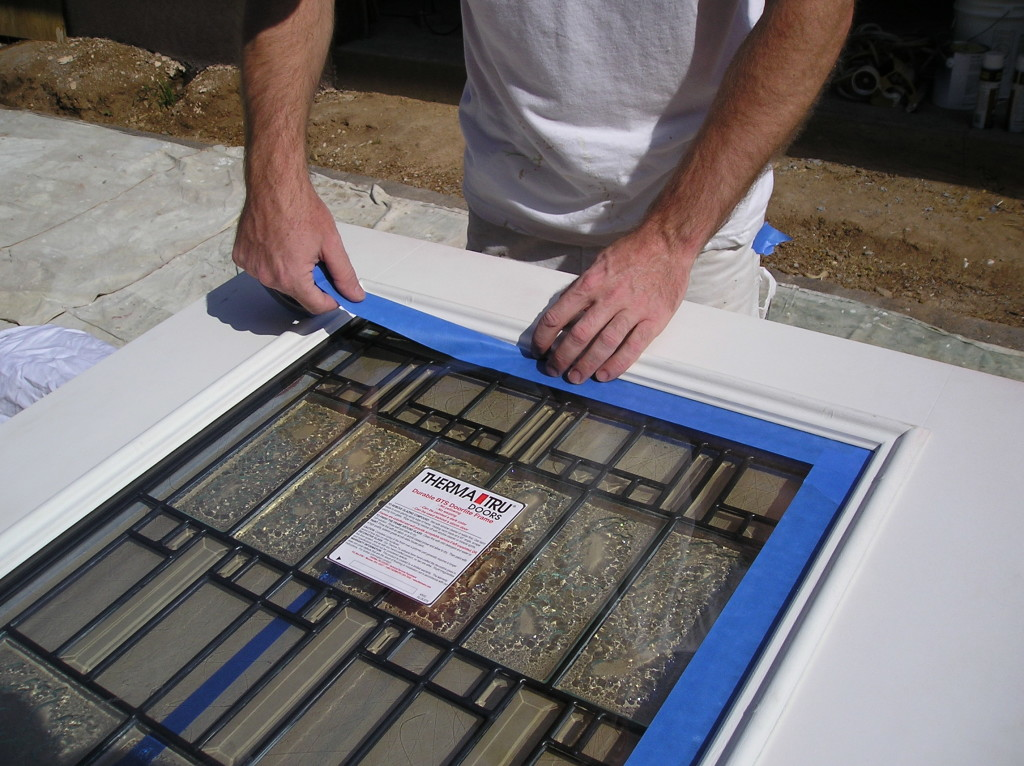 Masking a window before spraying a steel door.
