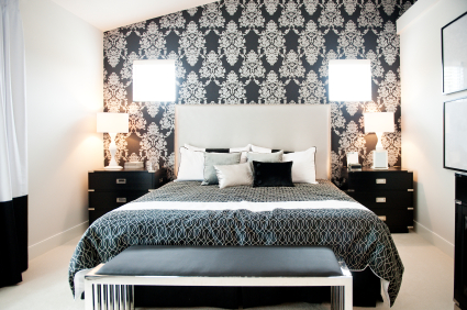 A modern bedroom with stylish wallpapered accent wall.