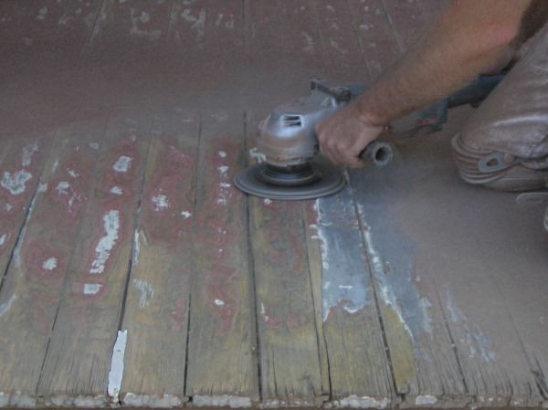 Using a large angle grinder with course sanding disk on painted porch floor.