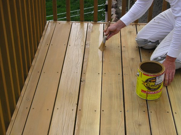 Staining the deck floor boards.