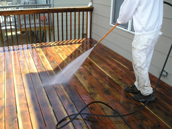 Low pressure washing a deck after sanding.