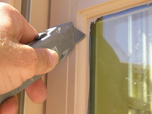 Removing excess paint from window glass..