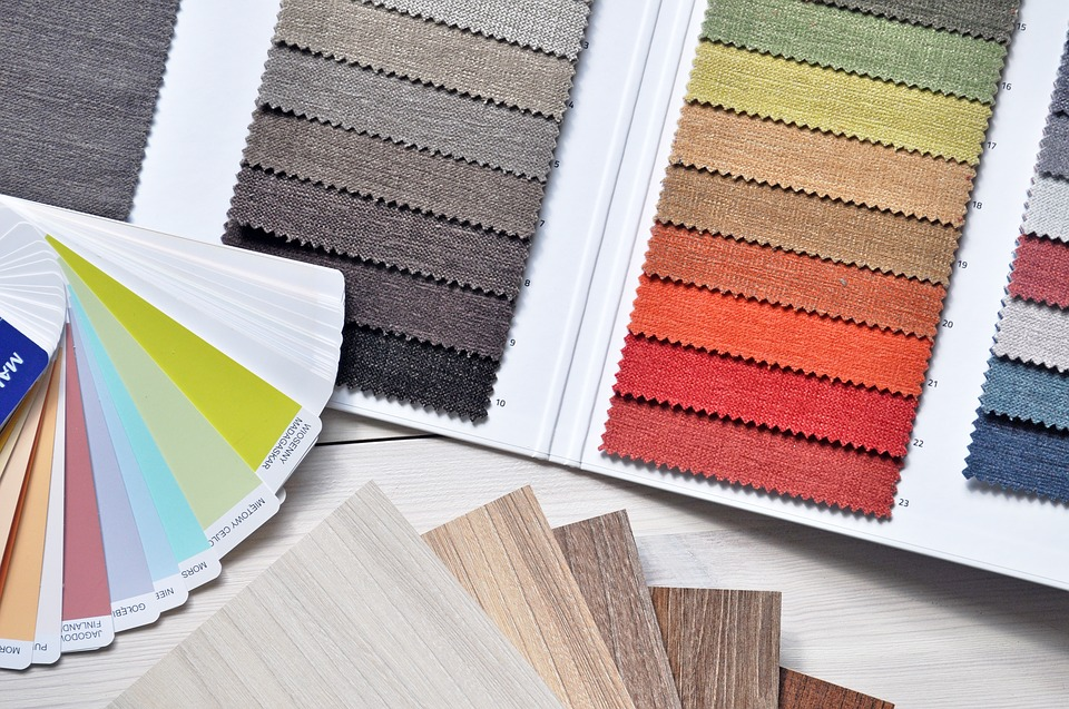 Choosing a color scheme using paint and interior design samples.