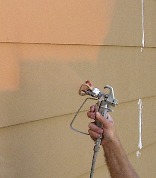 Airless paint spray gun angled to spray bottom siding lip.