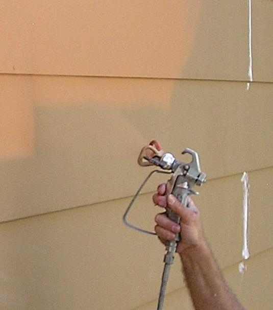 Airless spray gun angled to spray paint on siding lip.