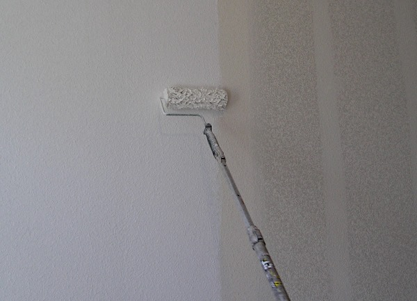 Applying drywall primer with a paint roller.