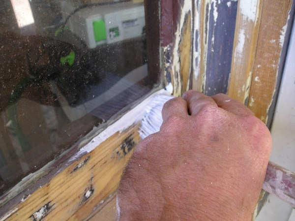 Priming a wood window sash and frame.