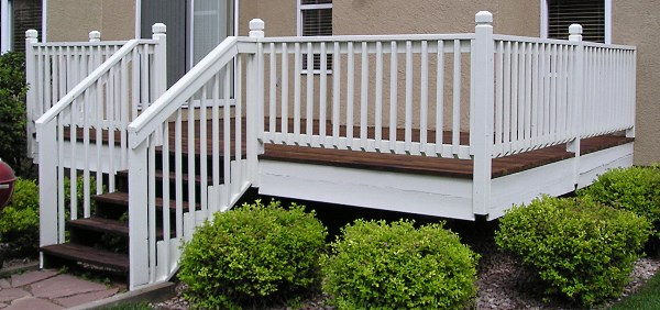 Newly refinished redwood deck with solid color handrails.