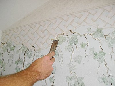 Removing a wallpaper border with putty knife.