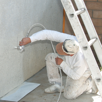 Spraying paint on stucco.