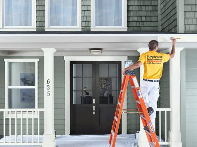 A man is painting the exterior of a home